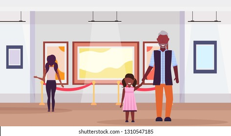family visitors in modern art gallery museum interior african american grandfather with granddaughter looking contemporary paintings artworks or exhibits flat horizontal full length