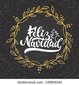 Feliz Navidad - lettering Christmas and New Year holiday calligraphy phrase on Spanish isolated on the chalkboard background with golden wreath. Fun brush ink typography