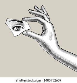 Female hand holds a mirror splinter in the fingers with eye reflection. Vintage engraving stylized drawing. Vector Illustration