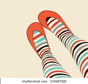 female legs in funny striped stockings and old-fashioned orange sandals
