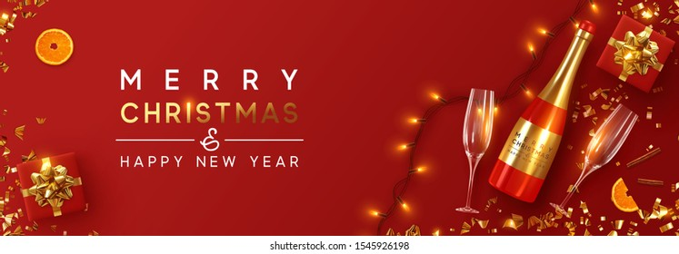 Festive Christmas background. Xmas design with realistic red bottle of champagne and wine, two glasses, sparkling lights garland, gift box, glitter gold confetti. Flat lay, top view. viewed from above