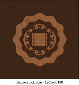 film icon inside badge with wood background