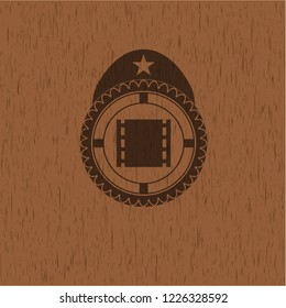 film icon inside retro style wooden emblem