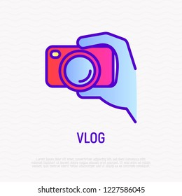 Filming vlog: camera in hand thin line icon. Modern vector illustration for video logo.