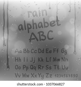 Finger draw alphabet on rain gray background. Water hand writing font template on glass surface