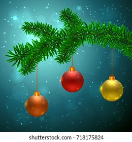 Fir tree with 3 Christmas balls: red, yellow and orange on dark blue background with bokeh effect