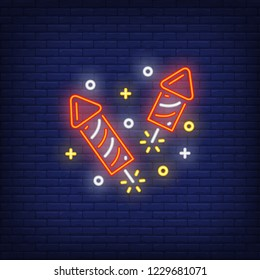 Firework neon sign. Glowing red petards with sparkles on dark blue brick background. Can be used for winter, christmas time, festive