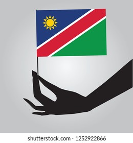 Flag of Namibia in a female hand. Vector illustration.
