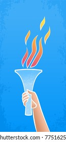 Flaming Torch. Human hand holding torch with a flame on blue sky background.