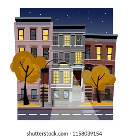 Flat cartoon vector illustration of autumn rainy city street at night. Uneven houses with luminous windows,. Street cityscape with glowing streetlight and starry sky. Town landscape with yellow trees