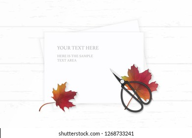 Flat lay top view elegant white composition paper autumn maple leaf and vintage metal scissors on wooden background.