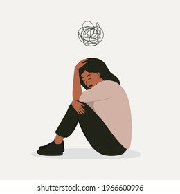 A flat vector cartoon illustration of a woman in a depressed mood, sitting on the floor and holding her knees, scribbling over her head. Mental health problems, burnout, depression.