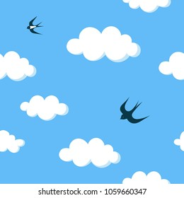 Flying barn swallows in the blue sky with white clouds seamless pattern