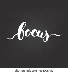 Focus - hand drawn lettering phrase, isolated on the chalkboard background. Fun brush ink inscription for photo overlays, typography greeting card or t-shirt print, poster design.