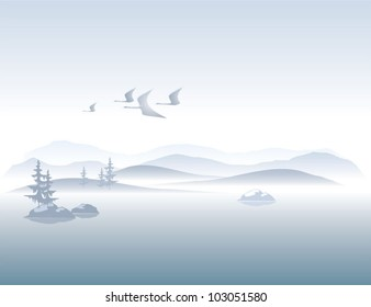 Foggy mountains on the lake peaceful landscape with flying cranes