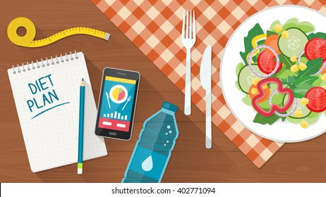 Food, diet, healthy lifestyle and weight loss banner with a dish of salad, table set, smartphone and diet plan on a notebook