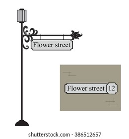Forged metal pointer streets with a lantern. Forged metal signboard. Wrought iron vintage sign.