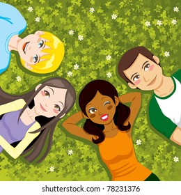 Four multi ethnic boys and girls friends resting happy together lying outdoors on a clover field
