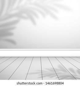 Fragment of an empty room with a white wall and floorboards. The shadow palm leaf shadows on top. Background for design