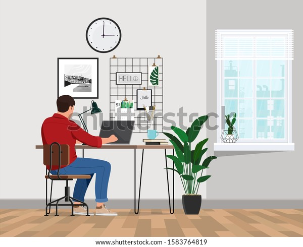 A freelancer man works behind a laptop. Home office workplace.