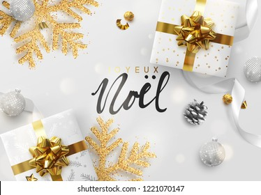 French text Joyeux Noel. Merry Christmas and Happy New Year. Design background composition top view. Decoration gift box, silver balls, decorative snowflake in glitter. Xmas bauble, white silk ribbon.