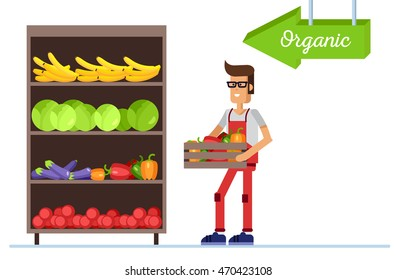 Friendly supermarket worker holds a box with vegetable. Vegetable department with food shelf.
