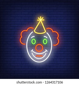 Funny clown face neon sign. Circus performance advertisement design. Night bright neon sign, colorful billboard, light banner. Vector illustration in neon style.
