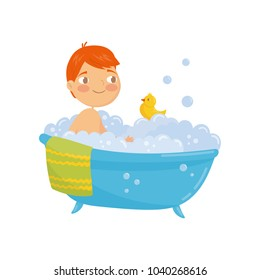 Funny red-haired boy taking bath with rubber duck toy. Bathtub with foam bubbles inside. Daily hygiene. Cartoon character of little child. Colorful flat vector design