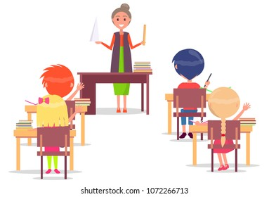 Geometry lesson in primary school. Children sit at desk and study alphabet at the lesson, teacher stands near blackboard with pointer