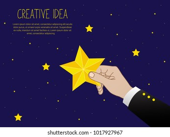 Get the star, reach height. Businessman holds a big yellow star isolated in background night sky.
