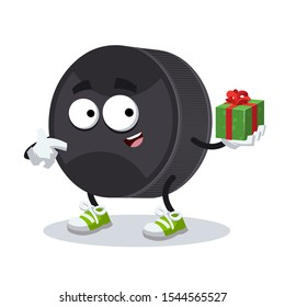 with gift box cartoon black rubber hockey puck character mascot smiling on white background