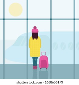 A girl in a bright yellow down jacket and a pink hat with a pink suitcase. A girl in the airport building , looking at the plane through the glass.