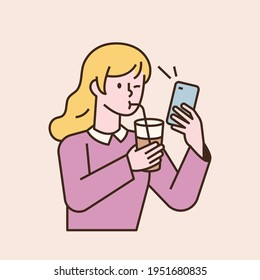 A girl is drinking a drink with a straw and looking at the phone. flat design style minimal vector illustration.