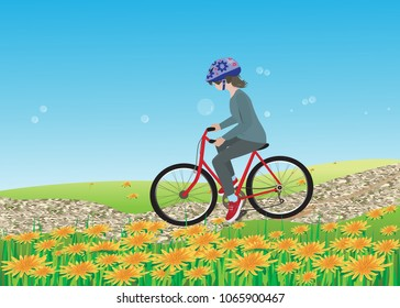 A girl with a helmet ride a bicycle through the dandelion field