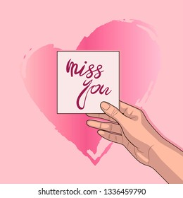 """Girl holds in her hand a piece of paper with typography lettering phrase """"miss you"""" on a pink background."""