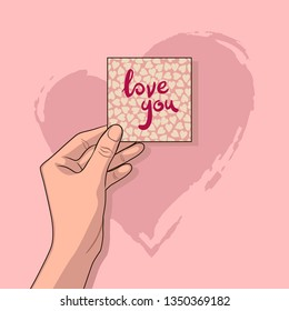 """Girl holds in her hand a piece of paper with typography lettering phrase """"love you"""" on a pink background."""
