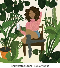 A girl holds a phone in her hand and shows it. A black girl in a pink sweater sits on a chair in a botanical garden surrounded by various plants and smiles.