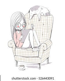 Girl reading a book in an armchair with a cat