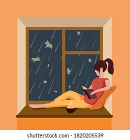 A girl sits by the window, reads a book and drinks tea while it is raining outside the window