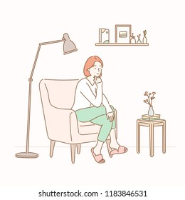 A girl sitting on a sofa in a room with a stand lamp and a small table. hand drawn style vector design illustrations.