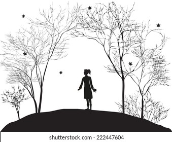 girl stands under the autumn trees and looks at te falling leaf, november come,