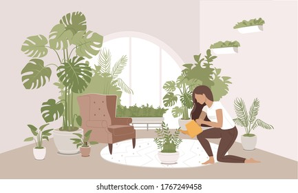 Girl taking care and watering ZZ plant with funnel at her home garden. Indoor gardening hobby. Jungles inspired interior in modern city apartment. Cozy and calming room decorated with many pot plants.