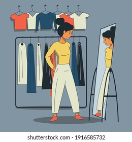 A girl tries on clothes in front of a mirror in a store. Buying fashionable clothes. Shopping.