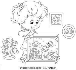 girl watching tropical fishes in an aquarium of a nature corner