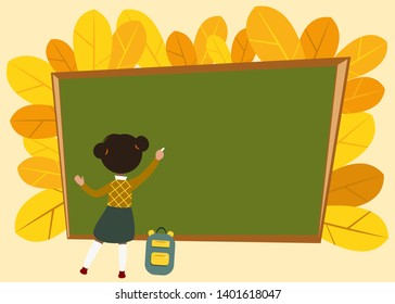 girl writing on a school board on a background of autumn yellow leaves