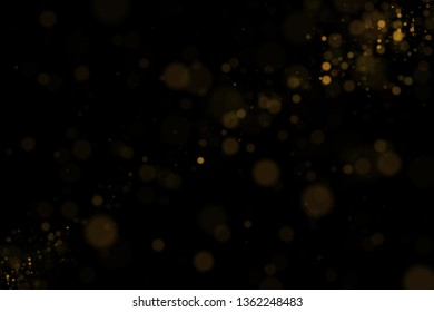 Glowing bokeh lights, shiny particles explode on black background