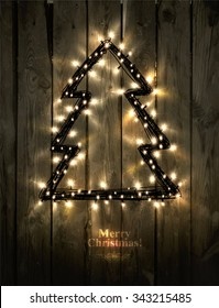 Glowing Christmas Tree made of led lights on the wooden background