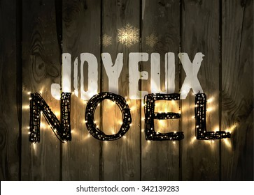 Glowing Christmas word NOEL made of led lights on the wooden background