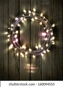 Glowing Christmas wreath made of led lights on the wooden background