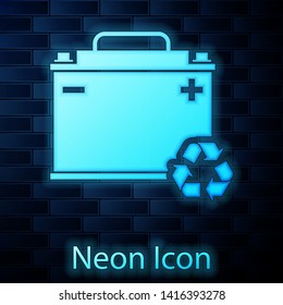 Glowing neon Car battery with recycle icon isolated on brick wall background. Accumulator battery energy power and electricity accumulator battery. Vector Illustration